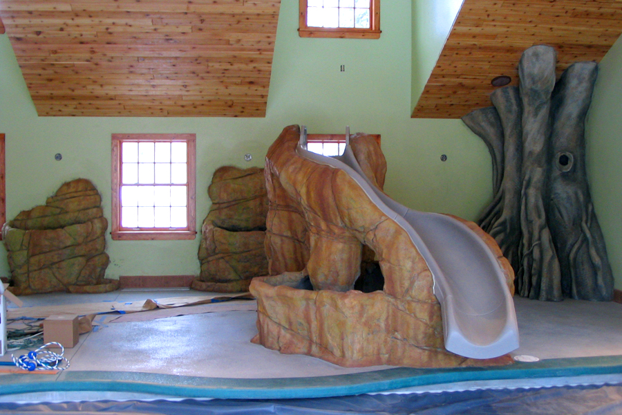 Custom poolside slide, rockery and tropical forest tree.